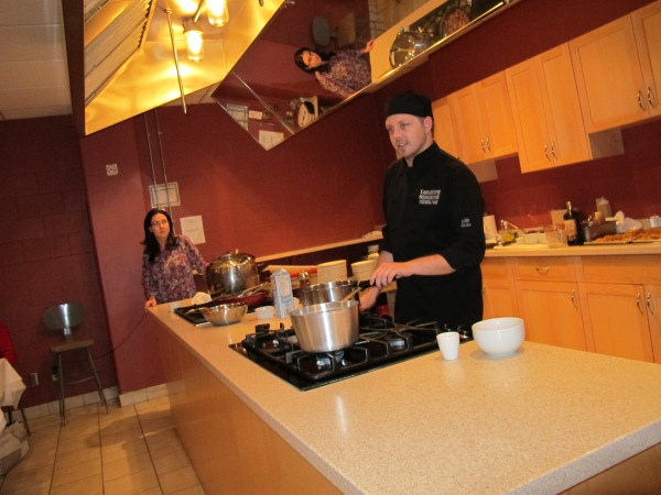 Chef Mitch Lamb prepares dinner while Dawn Nickerson from Bacchus Sommelier watches.